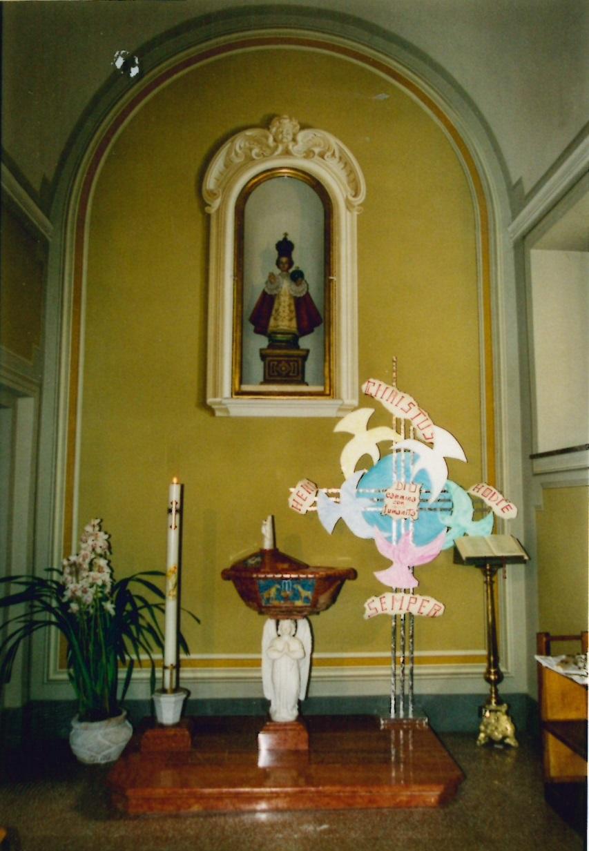 1. Il Battistero. Sulla parte la statua del Santo Bambino di Praga.