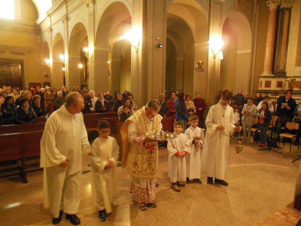 La processione formata dal celebrante e dai ministranti giunge all'altare. Don Mauro reca in mano il vassoio con i vasetti contenti gli Olii Santi.