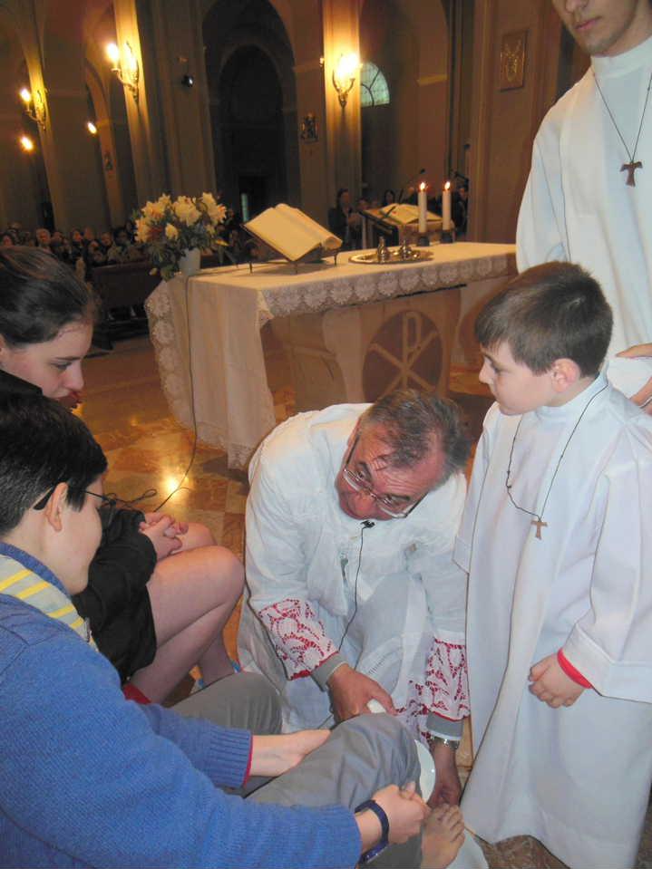 Dopo essersi tolto i paramenti e aver indossato il grembiule, don Mauro procede a lavare i piedi dei dodici prescelti.