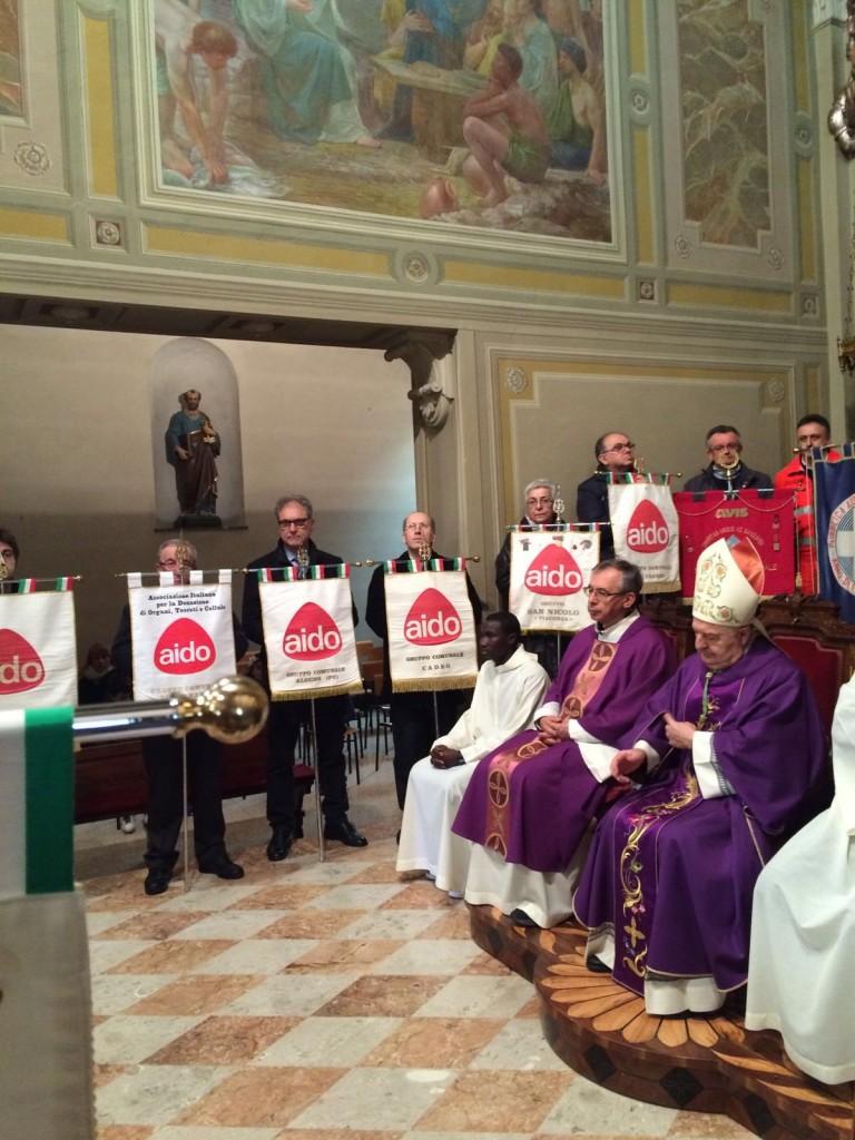 Monsignor Corbellini seduto a fianco di don Mauro. Attorno a loro i labari dei gruppi Aido della nostra provincia.