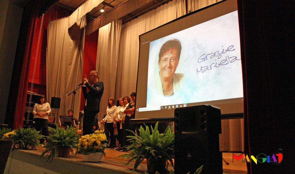 Il coro Perfetta Letizia e sullo schermo una bella foto di Mariella.