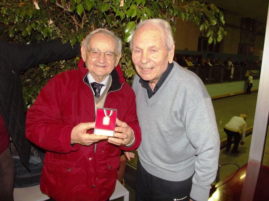 Luigi Benaglia, in rappresentanza della Valcolatte, mostra la medaglia d'oro in posa per una foto insieme al presidente della Bocciofila OMI; Bruno Cagni.
